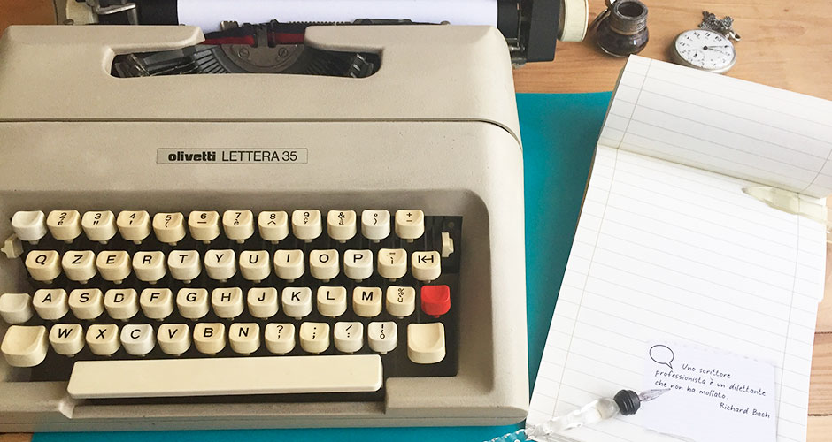 """Copertina della rubrica """"La voce dello scrittore"""", che ritrae una macchina da scrivere, un blocco dello scrittore, un orologio da tasca, una penna di cristallo e una boccetta per inchiostro"""