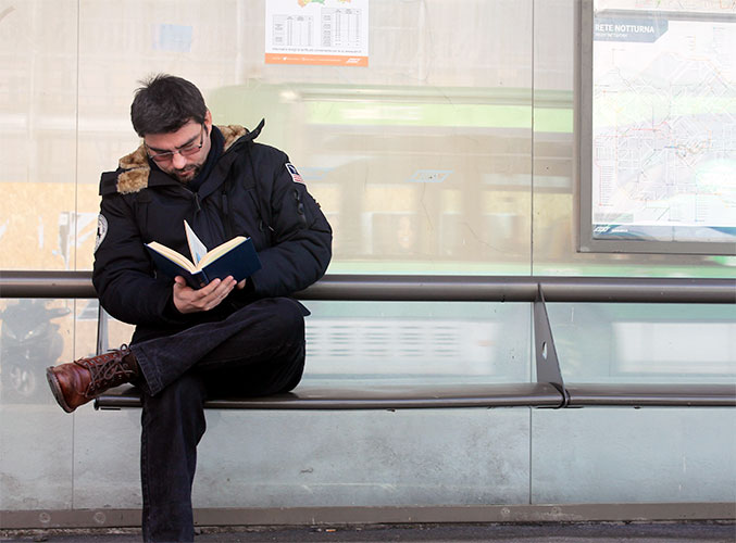Un lettore è seduto alla fermata del bus ed è intento a leggere, senza accorgersi che l'autobus è appena passato
