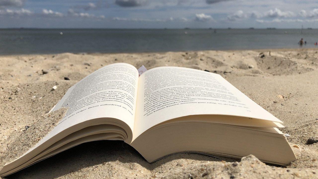 Un libro aperto e posato sulla spiaggia